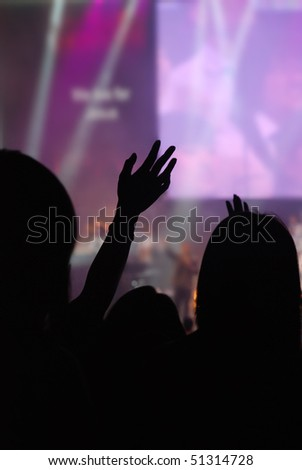 christian music concert with raised hand - stock photo