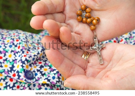 Christian prayer beads and crucifix in the hands of old woman  - stock photo