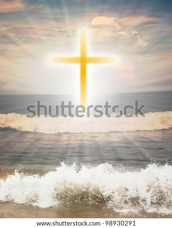Christian religious symbol cross against sun shine  in the background and waves from the ocean in the foreground - stock photo