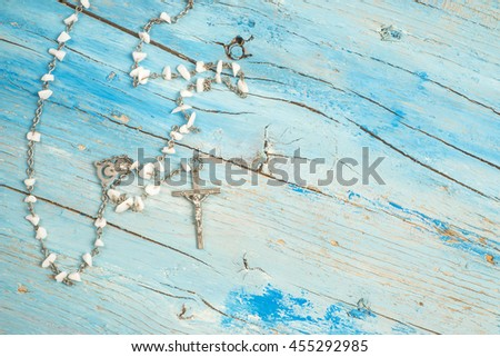Christian rosary on blue rustic wood with blank space - stock photo