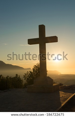 Christian stone cross under the warm light of sunrise - stock photo