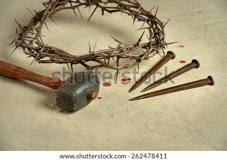 Christian symbols of the crucifixion with crown of thorns, nails and mallet on distressed cloth - stock photo