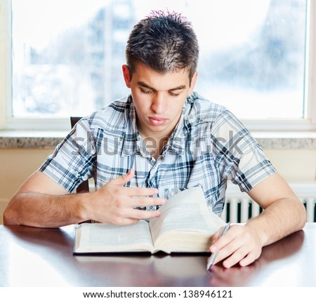 Christian teenager in his daily devotional. Young man reading the Holy Bible - stock photo