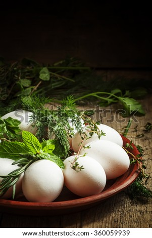 Christian tradition dyeing Easter eggs with a pattern of herbs, eggs and herbs on a clay plate in a rustic style, selective focus - stock photo