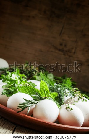 Christian tradition dyeing Easter eggs with a pattern of herbs, eggs and herbs on a clay plate in a rustic style, selective focus