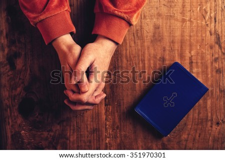 Christian woman praying with hands folded and fingers crossed, Holy Bible by her side on wooden desk in church, top view - stock photo