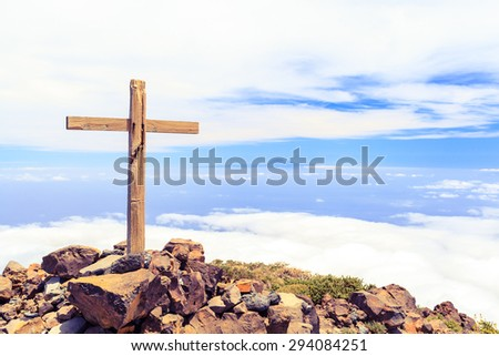 Christian wooden cross on mountain top, rocky summit, beautiful inspirational landscape with ocean, island, clouds and blue sky, looking at scenic blue sea and white clouds. - stock photo
