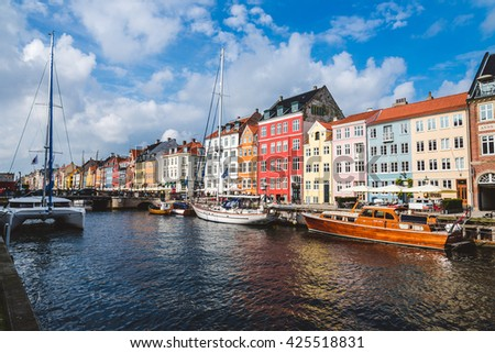 Christianshavn harbor in Copenhagen, Denmark - September, 24th, 2015. Colorful scandinavian houses and private boats reflected on the water of canal
