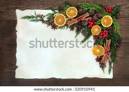 Christmas abstract background border with dried fruit and spice, holly, ivy, cedar cypress and fir on parchment paper over old oak wood. - stock photo