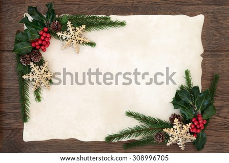 Christmas abstract background border with snowflake bauble decorations, holly, ivy and fir on parchment paper over old oak wood. - stock photo