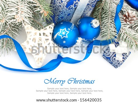 Christmas accessories in blue & fir tree branch on white - stock photo