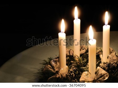 Christmas advent wreath with burning candles laid on table with black background - stock photo