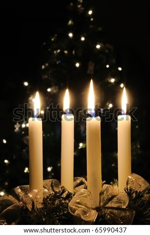 Christmas advent wreath with burning candles. Lights on x-mas tree in background - stock photo