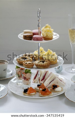 Christmas afternoon tea with turkey and cranberry sandwiches, crayfish cocktails, salmon bilinis, mince pies, cupcakes and macaroons - stock photo