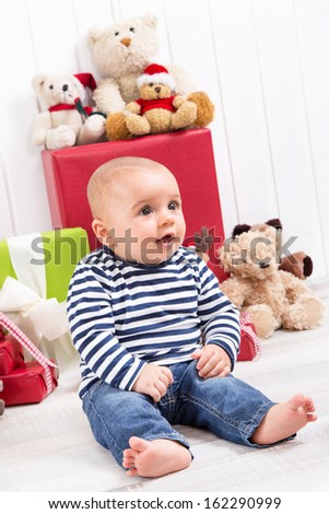 Christmas and birthday - cute baby sitting barefoot and looking excited surrounded by teddy bears and presents