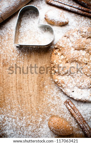 Christmas and holiday baking background, flour, bakeware, heart, cinnamon, cookies and almonds on a wooden board, viewed from above - stock photo