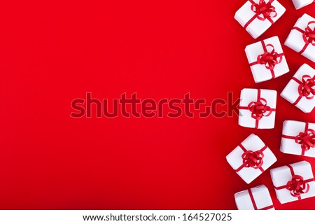 Christmas and holidays background with presents on red surface, copy space - stock photo