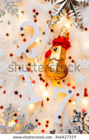 Christmas and New Year background with numbers 2017, decorations and light bulbs. Symbol of year - golden fiery rooster. - stock photo