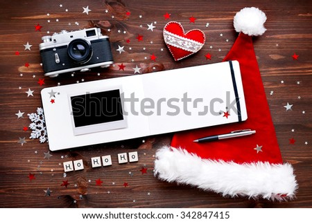 "Christmas and New Year background with old fashioned camera, Santa's hat, notepad, photo frame and decorations - stars, silver snowflakes, confetti and words ""Ho Ho Ho"". Place for your text. Mock up. - stock photo"