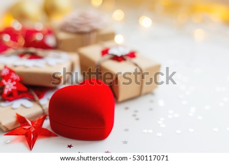 Christmas and New Year background with red box in shape of heart and presents, decorations for Christmas tree. Holiday background with stars confetti and light bulbs. Place for text.