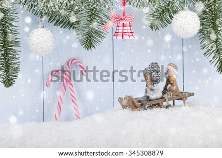 Christmas and New Year background with smiling figurines on the sledge, Christmas decorations and candy canes - stock photo