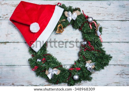 Christmas and New Year background with wreath and Santa hat on white vintage wooden plank