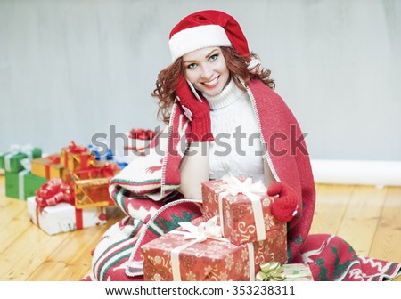 Christmas and New Year Celebration and Concepts. Happy Looking Red-Haired Caucasian Woman in Santa Hat Surrounded by Plenty of Gifts Speaking by Cellphone Indoors. Horizontal Image