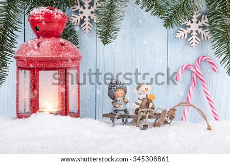 Christmas and New Year concept background with smiling figurines, Christmas lantern and candy canes - stock photo