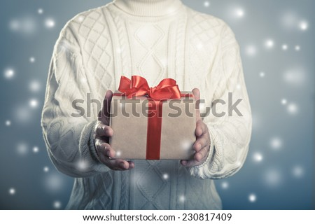 Christmas and new year concept. Male giving close up red ribbon giftbox on the snowy background. - stock photo