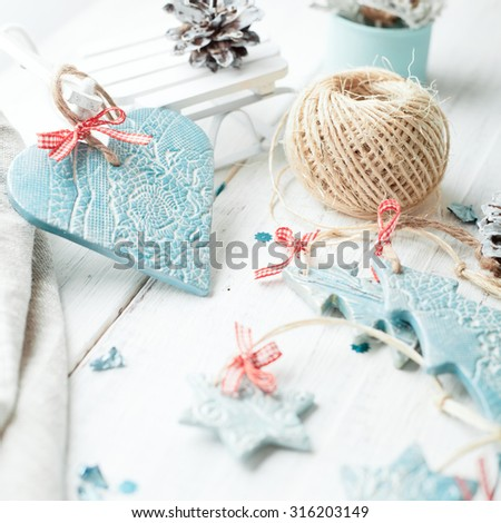Christmas and New Year decorations - candles, hand made ceramic decor (heart, tree and star) and pine tree cones, on wooden table. Lightly toned photo.  - stock photo