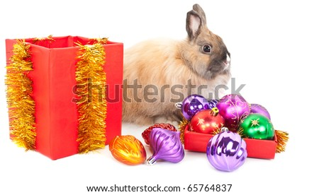 Christmas and new-year decorations.  Rabbit, red giftbox and  many varicoloured ball  composition on a white background - stock photo