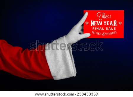 Christmas and New Year discounts topic: Hand of Santa Claus holding a red card with a Christmas discount on an isolated dark blue background - stock photo
