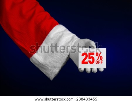 Christmas and New Year discounts topic: Hand of Santa Claus holding a white card with a 25 percent discount on an isolated dark blue background - stock photo