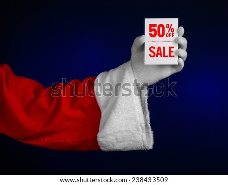 Christmas and New Year discounts topic: Hand of Santa Claus holding a white card with a 50 percent discount on an isolated dark blue background - stock photo