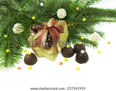 Christmas and New Year still life with decorated gift box, natural conifer branches and round chocolate candies, isolated on white - stock photo