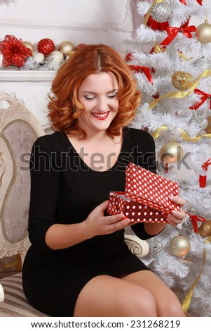 Christmas and New Year. Woman with a gift box in the beautiful interior with a Xmas tree