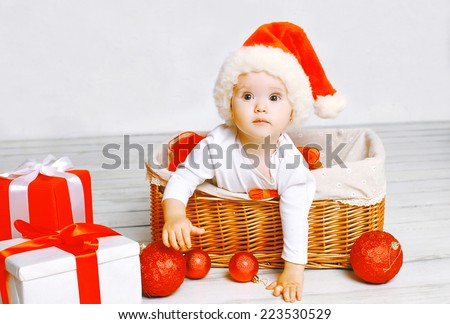 Christmas and people concept - charming baby with gifts