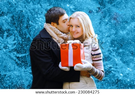Christmas and people concept - happy man giving a box gift and kissing to a woman, happy pretty couple in winter snowy day - stock photo