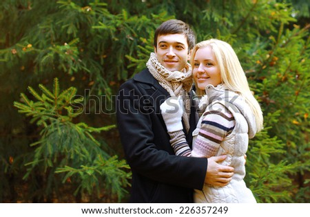 Christmas and people concept - happy pretty couple against christmas tree in winter day - stock photo