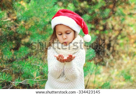 Christmas and people concept - little girl child in santa red hat blowing on snow in hands - stock photo