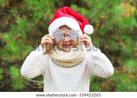Christmas and people concept - little girl child in santa red hat with snowflakes on the eyes - stock photo