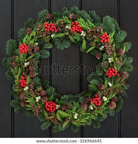 Christmas and winter wreath with holly, mistletoe, pine cones and blue spruce fir over dark blue oak  front door background. - stock photo