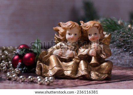 Christmas angels singing and playing on the harp and trumpet. Sitting on the wood. Christmas green wreath and purple, pink Christmas Balls with golden, shiny Christmas chain on the background.  - stock photo