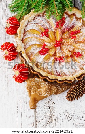christmas apple pie and christmas decorations on festive table. - stock photo