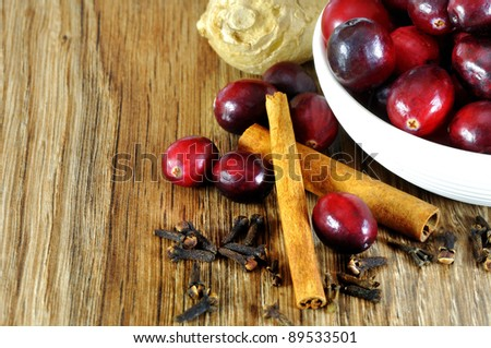 christmas aroma spices, cinnamon, cranberries, ginger and cloves needed for the Christmas dishes - stock photo