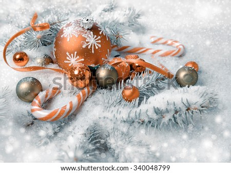 Christmas arrangement in orange and green on christmas tree twigs under snow. Merry Christmas! - stock photo