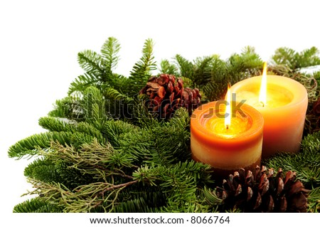 Christmas arrangement of burning candles and green spruce branches on white background - stock photo