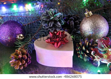 Christmas arrangement of fir branches, cones, shiny balls, garlands with multicolored lamps and gift box with a red bow.