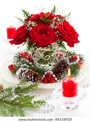 Christmas arrangement of red roses,fir, holly and pine cones - stock photo
