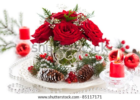 Christmas arrangement of red roses,fir, holly and pine cones